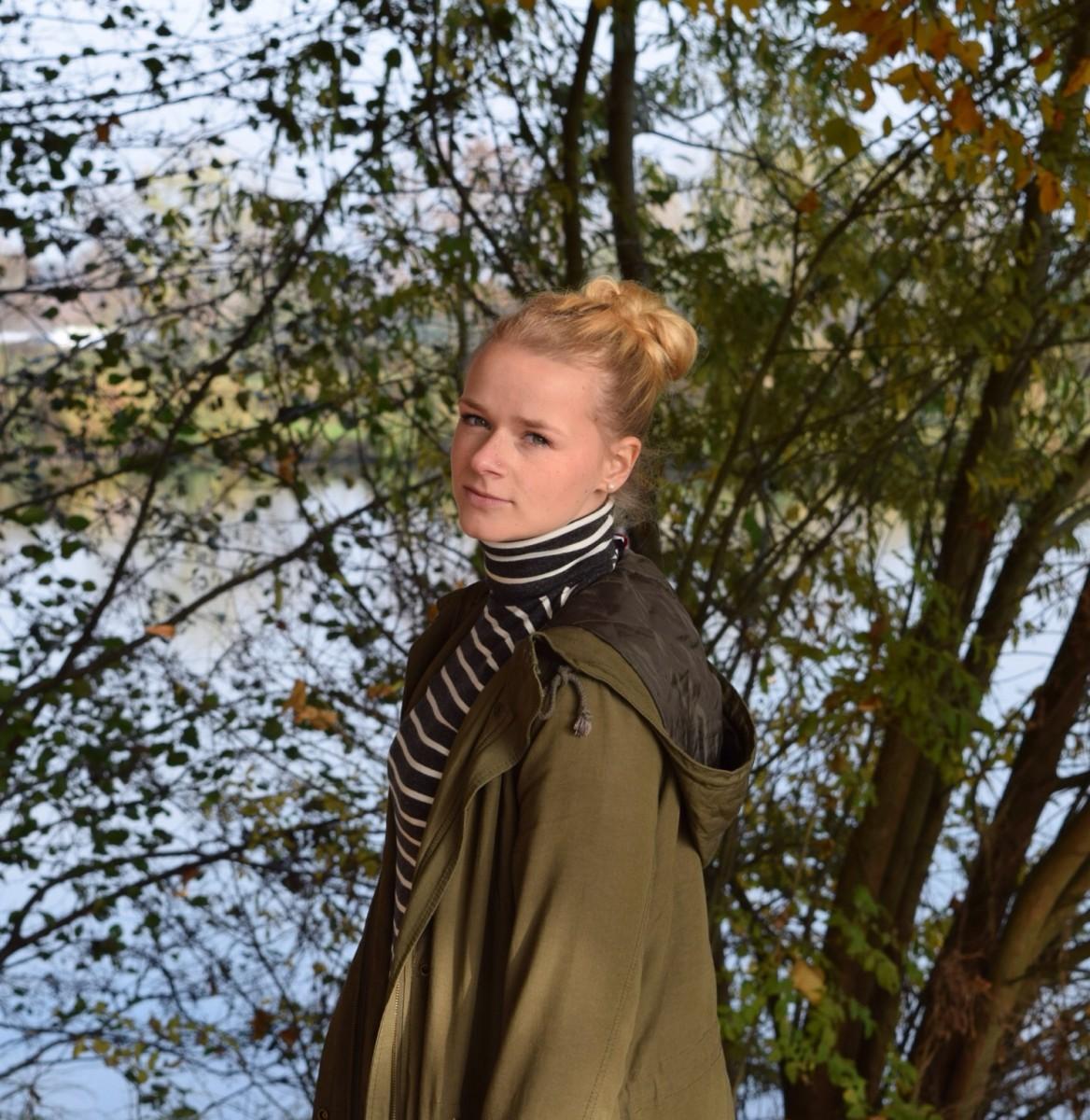 blonde-haare-herbst-blätter-grüner-parka-gestreifter-rollkragenpullover
